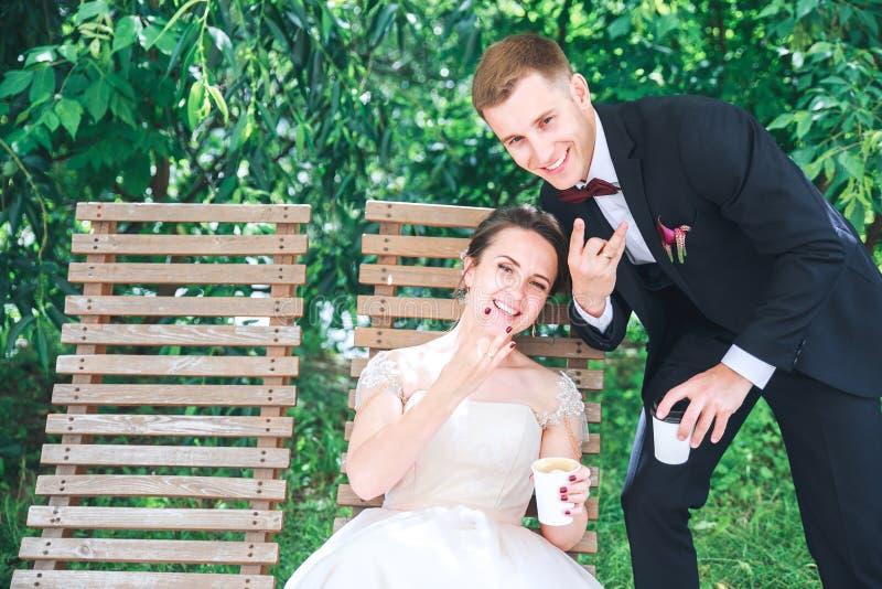 年轻美丽的新娘和新郎饮用的咖啡在户外咖啡馆 日愉快的婚礼 免版税图库摄影