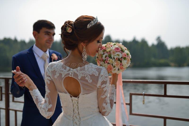 美丽的新娘嗅到婚礼花束,握她的手的时髦的新郎在背景 免版税库存图片