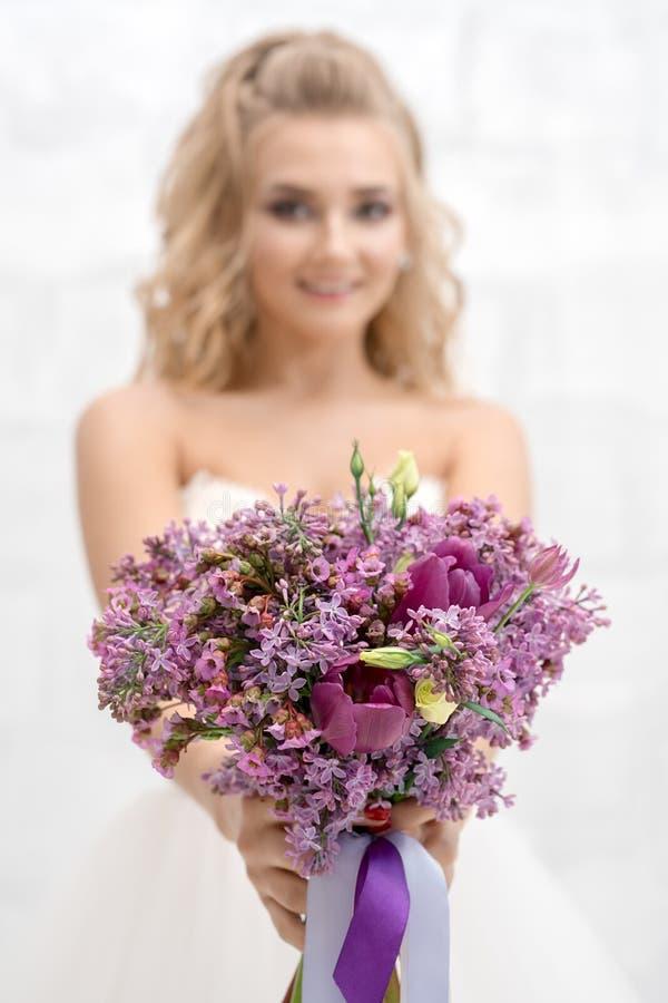美丽的新娘在有精妙的花束的演播室 库存照片