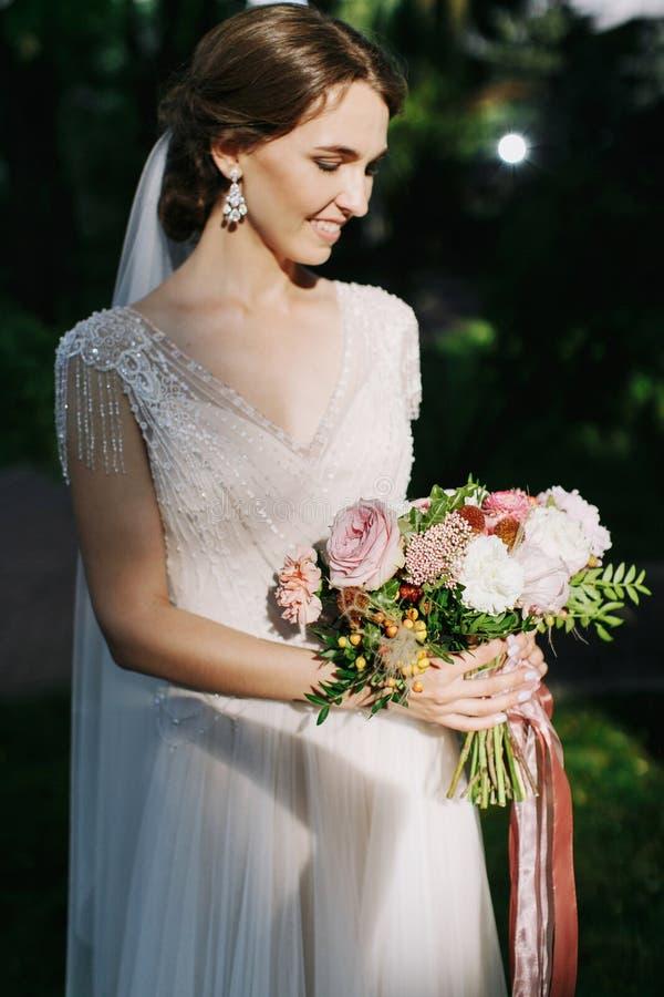 美丽的新娘拿着在鞋带礼服的婚礼五颜六色的花束有小珠的 色的花秀丽  特写镜头 免版税库存照片