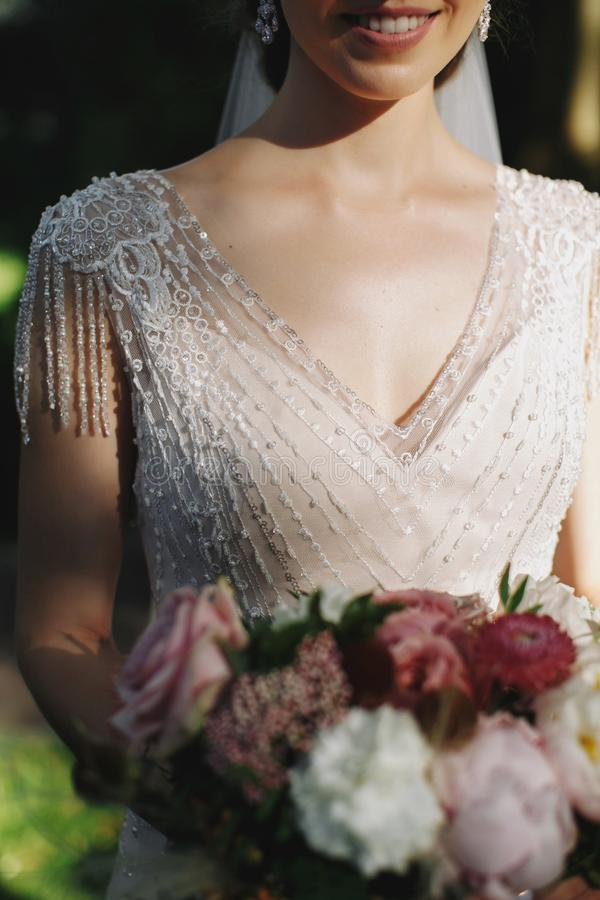 美丽的新娘拿着在鞋带礼服的婚礼五颜六色的花束有小珠的 色的花秀丽  特写镜头 brewster 免版税库存图片