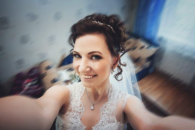 美丽的新娘时尚照片有黑发的在摆在屋子里的典雅的婚纱在婚姻的早晨 库存图片