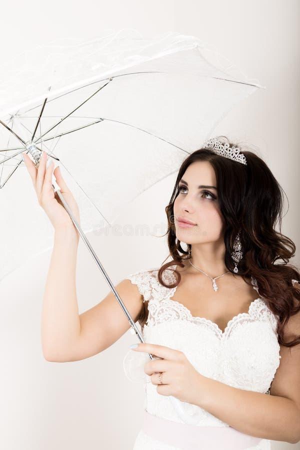 年轻美丽的新娘特写镜头画象一套婚礼礼服的与婚礼构成和发型 举行白色的女孩 库存图片