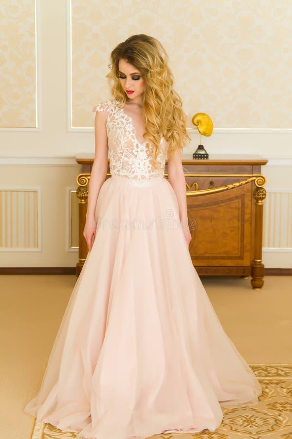 美丽的新娘纵向年轻人 女孩在旅馆客房摆在 夫人在她的婚礼礼服转动 免版税库存照片