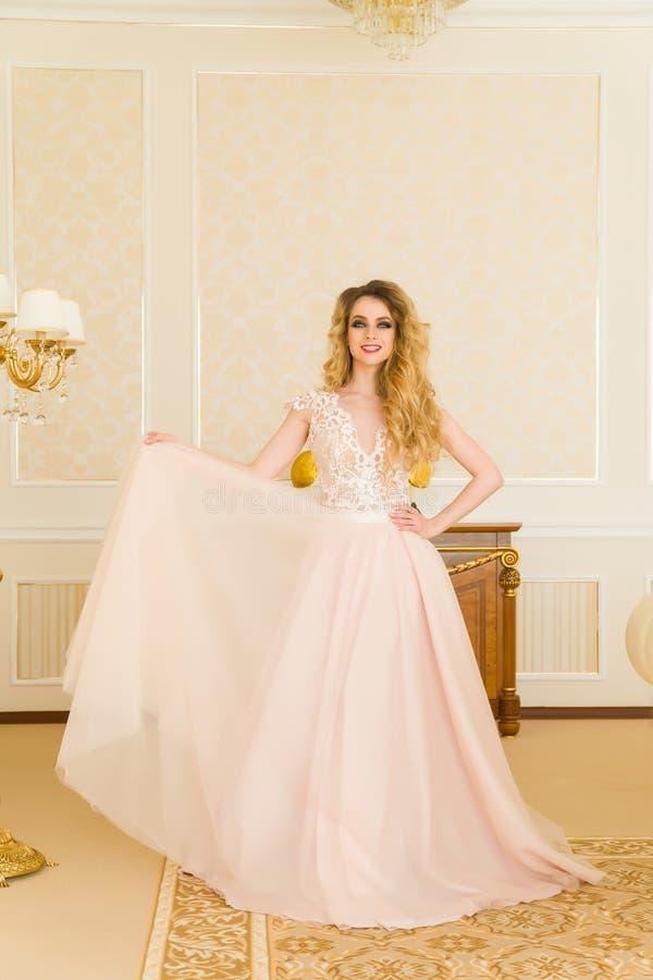 美丽的新娘纵向年轻人 女孩在旅馆客房摆在 夫人在她的婚礼礼服转动 库存照片