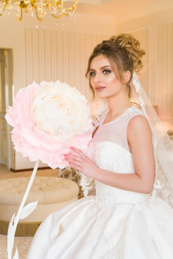 美丽的新娘纵向年轻人 女孩在旅馆客房摆在 夫人坐与一朵纸花由窗口 免版税库存图片