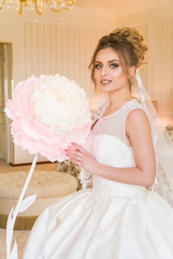美丽的新娘纵向年轻人 女孩在旅馆客房摆在 夫人坐与一朵纸花由窗口 免版税库存照片