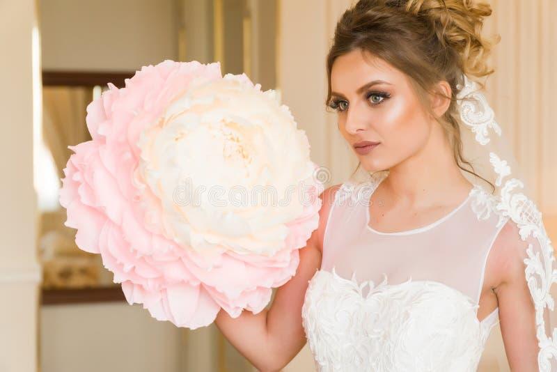 美丽的新娘纵向年轻人 女孩在旅馆客房摆在 夫人坐与一朵纸花由窗口 库存图片