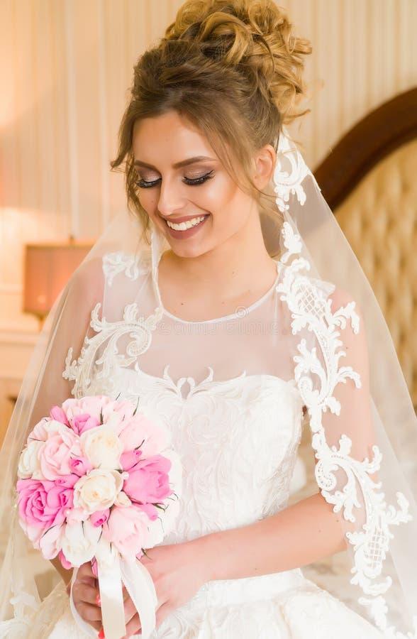 美丽的新娘纵向年轻人 女孩在旅馆客房摆在 夫人坐与玫瑰花束由 免版税库存图片
