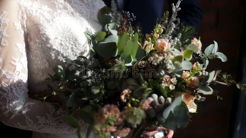美丽的新娘花束在年轻新娘的手上在白色婚礼礼服穿戴了 接触婚礼花束的新娘手 免版税库存图片