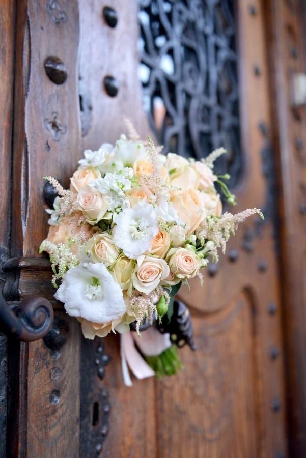 美丽的新娘花束在门把手说谎 库存图片