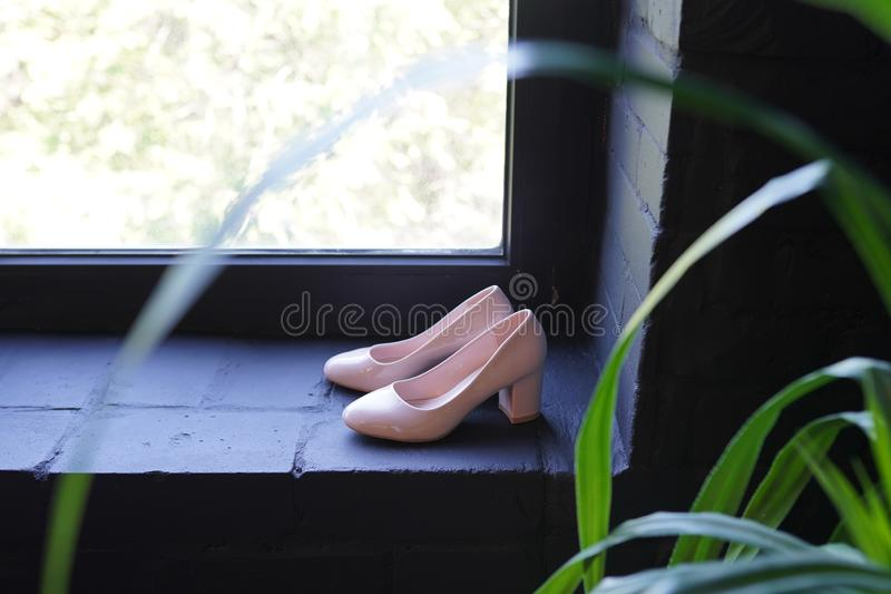 美丽的新娘金黄短剑鞋子 豪华在黑暗的窗口的设计师婚姻的鞋子 图库摄影