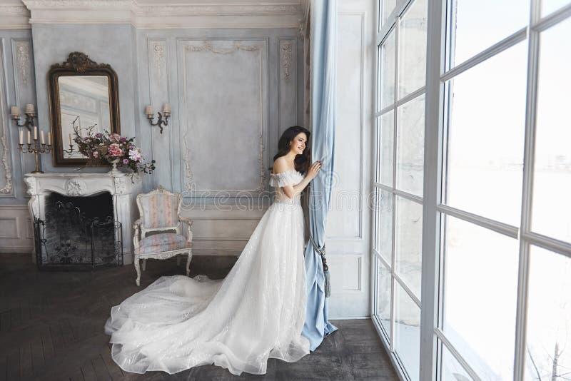 美丽的新娘,年轻式样深色的妇女,与赤裸肩膀的时髦的婚礼礼服的,与花花束  免版税库存图片