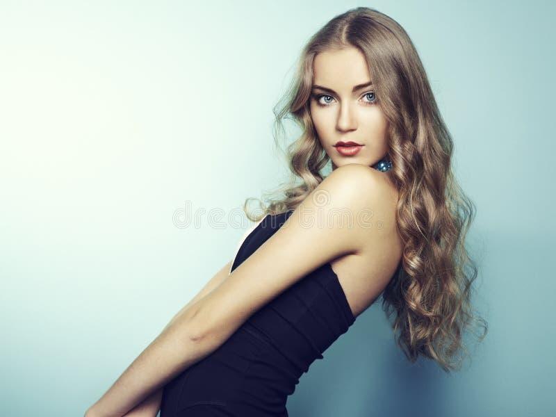 美丽的新白肤金发的女孩纵向黑色礼服的 免版税库存图片