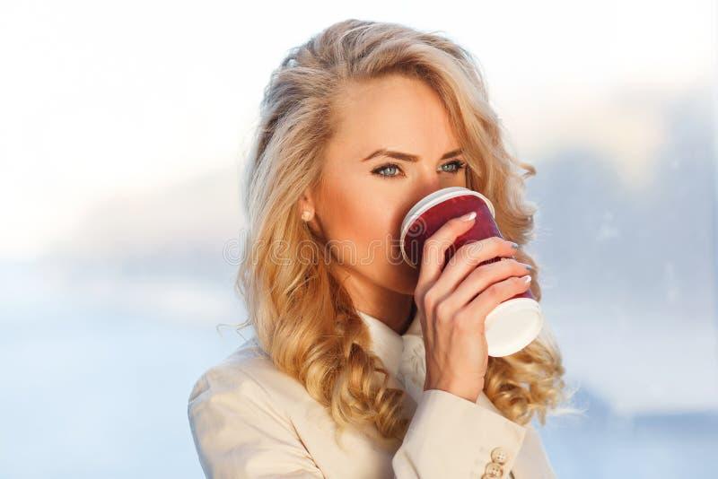 美丽的新鲜的白肤金发的妇女饮用的咖啡特写镜头画象  免版税库存照片