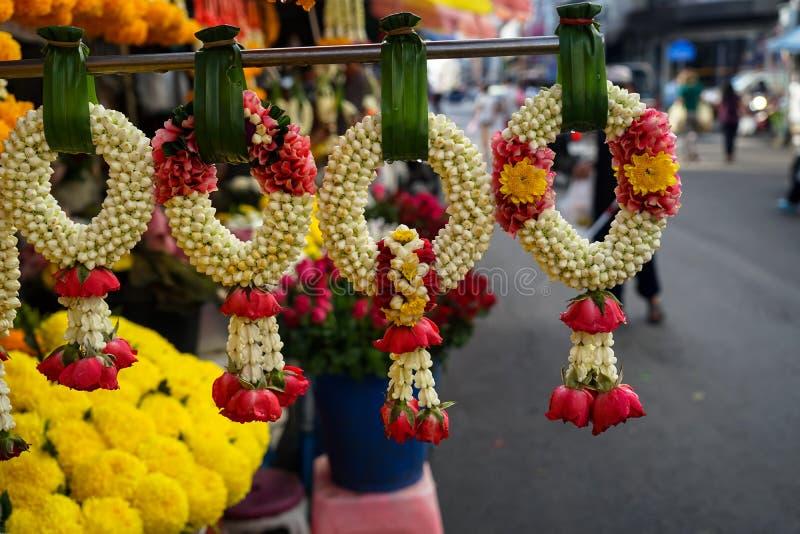 美丽的新鲜的详尽阐述的花诗歌选行在垂悬在pandan叶子的泰国样式的有地方早晨市场背景 免版税图库摄影