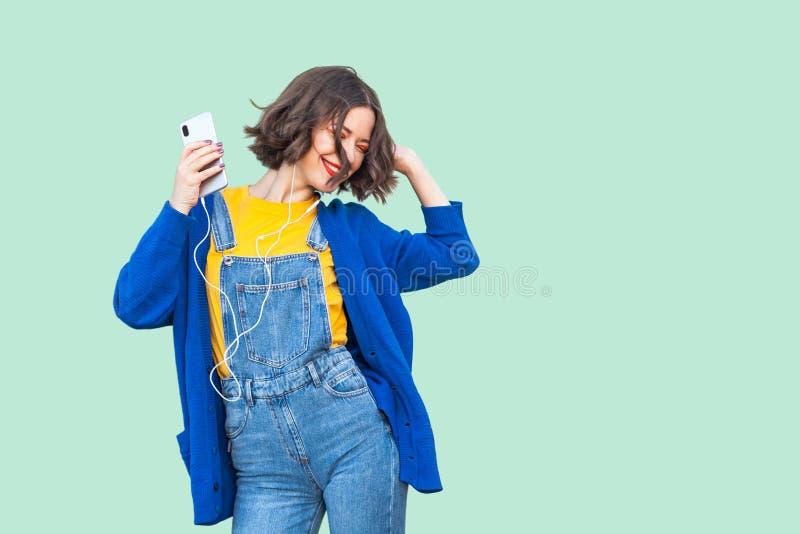 美丽的无忧无虑的年轻妇女画象行家穿戴的在听牛仔布的总体站立,拿着电话和她 免版税库存照片
