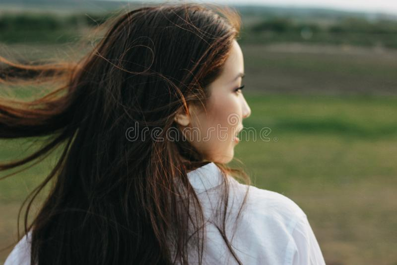 美丽的无忧无虑的长发女孩接近的画象白色衣裳的在自然领域,从后面的看法 ?? 图库摄影