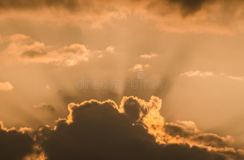 美丽的日落太阳发出光线击穿通过在橙色天空的蓬松云彩在一个热的夏日黄昏 令人敬畏的cloudscape背景 库存图片