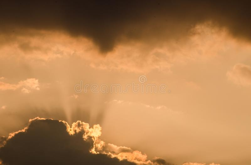 美丽的日落太阳在一个热的夏日发出光线击穿通过在橙色天空的云彩在黄昏 令人敬畏的cloudscape backgrou 免版税库存图片
