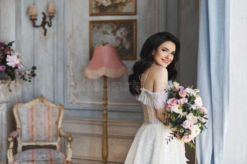 美丽的时兴的新娘,时髦的婚礼礼服的年轻式样深色的妇女与与花花束的赤裸肩膀在h的 免版税库存照片
