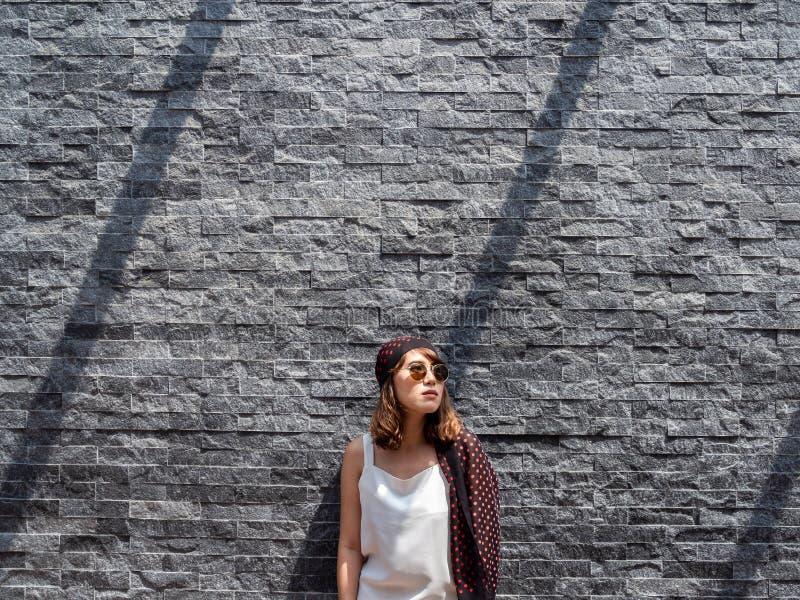 美丽的时兴的现代灰色砖墙纹理背景的行家亚裔妇女 免版税图库摄影
