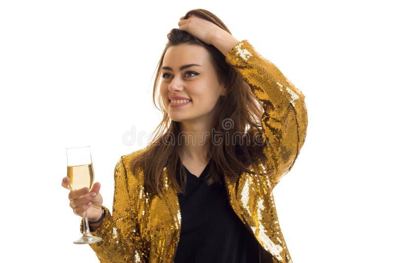 美丽的时尚女孩金夹克微笑并且拿着一杯酒 图库摄影