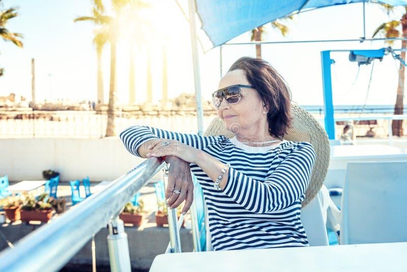美丽的时髦的年长妇女在一条游艇旅行,在backgro 免版税库存照片