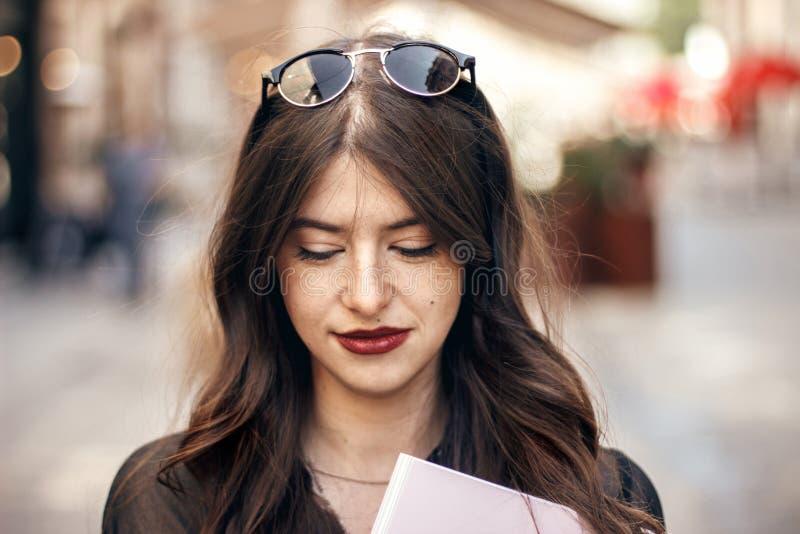 美丽的时髦的行家女孩微笑在晴朗的城市街道的, hol 免版税库存照片