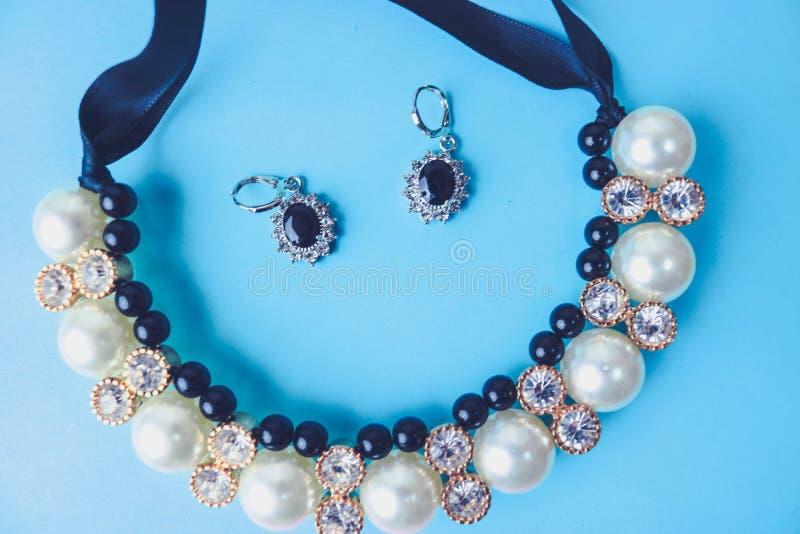 美丽的昂贵的珍贵的发光的首饰时兴的迷人的首饰、项链和耳环有珍珠和金刚石的 免版税库存照片