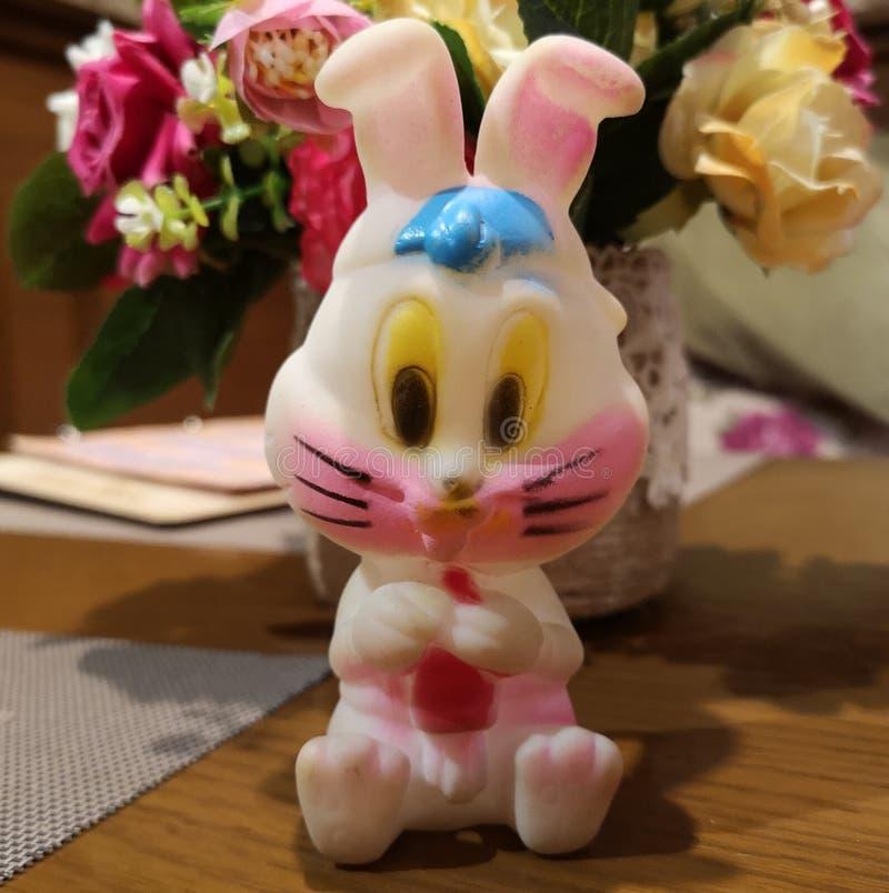 美丽的明亮的塑料野兔坐花背景  库存照片