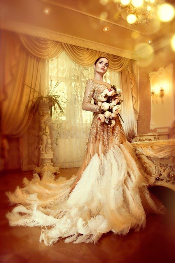 美丽的晚礼服的秀丽华美的妇女在豪华样式内部室 免版税图库摄影