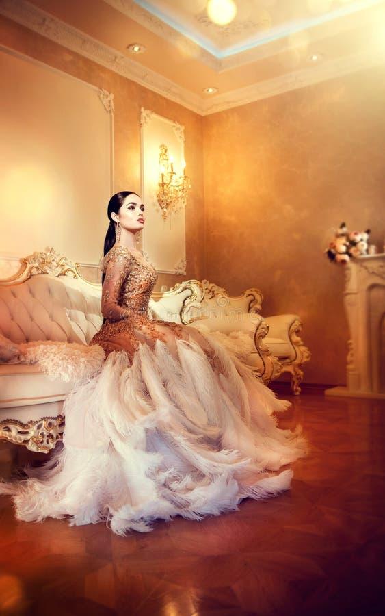 美丽的晚礼服的秀丽华美的妇女在豪华样式内部室 库存照片