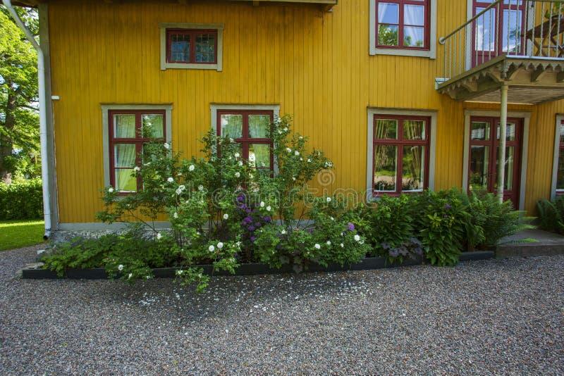 美丽的景色frontsize黄色木房子whith花在窗口下 r 免版税图库摄影