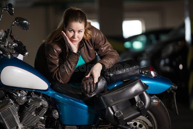 美丽的有一辆经典摩托车的摩托车深色的妇女,棕色泡沫夹克 库存照片