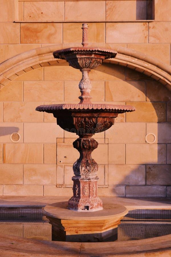 美丽的有两个水平的葡萄酒中世纪喷泉在一个老大厦前面 免版税库存图片