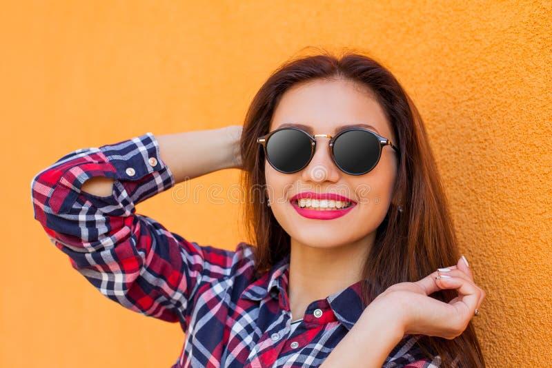 美丽的有反射的妇女和太阳镜特写镜头画象有完善的构成的,微笑 橙色背景 免版税库存照片