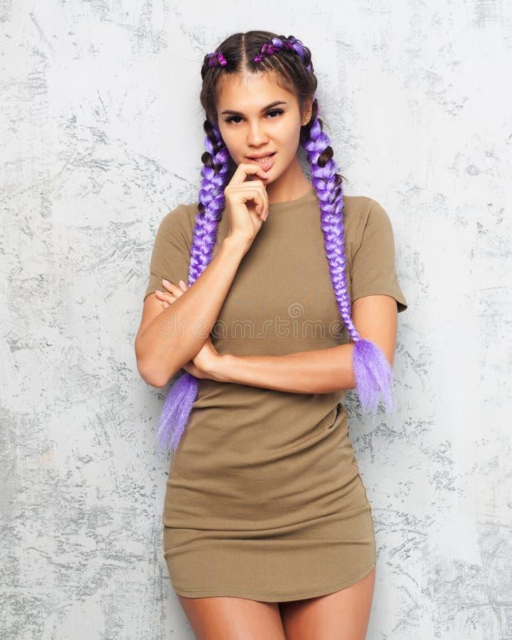美丽的有穿礼服的紫色辫子的行家想法的女孩摆在灰色背景 库存照片
