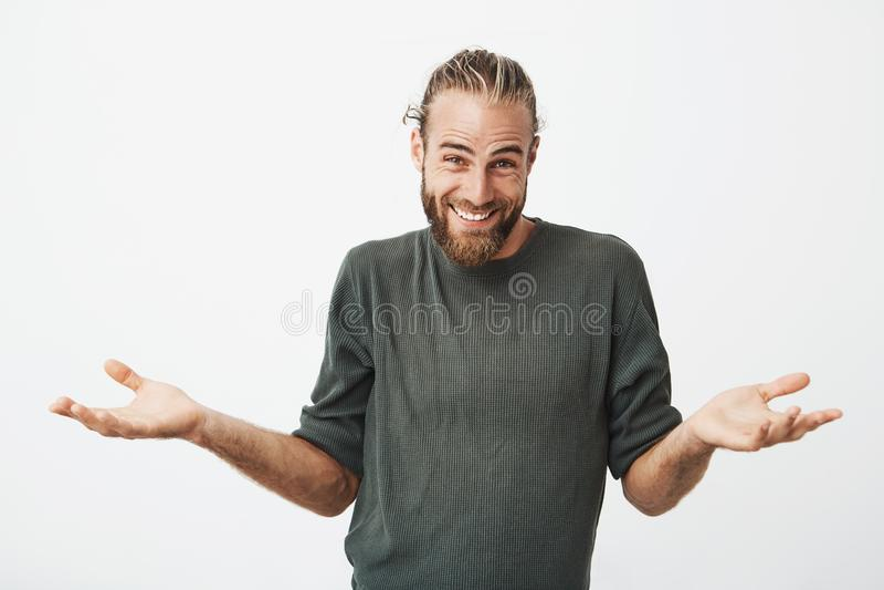 美丽的有胡子的人用时髦的发型微笑的和传播的手在答复穿上` t知道怎样说 肢体语言 免版税库存照片