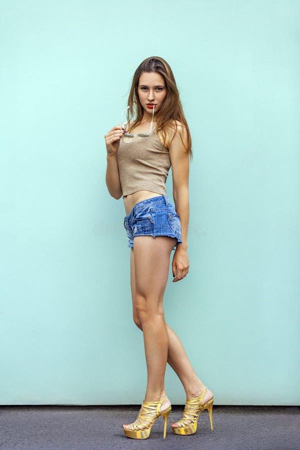 美丽的有雀斑的女孩 简而言之典雅的时装模特儿,偶然上面和金黄鞋子,反对在蓝色背景的肉欲的姿势 库存图片