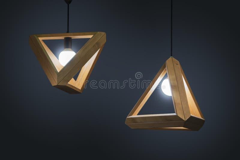 美丽的木几何现代在黑暗的背景隔绝的天花板灯内部当代装饰 免版税库存图片