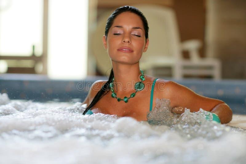 美丽的极可意浴缸妇女年轻人 免版税库存图片