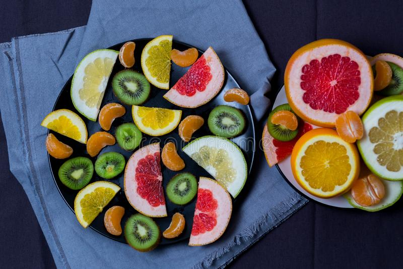 美丽的柑橘橙色葡萄柚普通话糖果猕猴桃柑橘削减了切片的片断在大板材黑色的切片和 免版税图库摄影