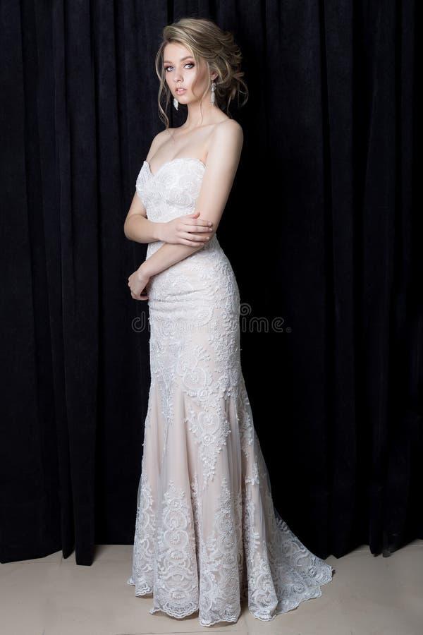 美丽的柔和的一件美丽的鞋带礼服的女孩性感的新娘有有晚上发型和构成的一列火车的在blac的演播室 图库摄影