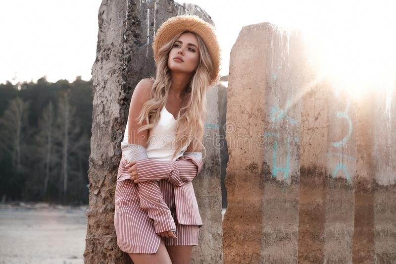 美丽的柔和的少女在草帽在阳光下摆在 乡下风景,在背景的森林自然 ?? 免版税库存图片