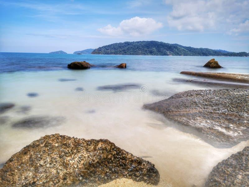 美丽的柔滑的光滑的水波和岩石在海岸 免版税库存图片