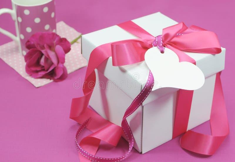 美丽的桃红色和白色礼物盒当前与咖啡杯 免版税图库摄影