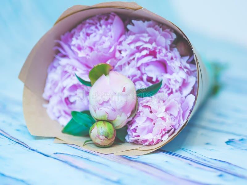 美丽的桃红色牡丹花束在一张蓝蓝木桌上的反对软被聚焦的背景 免版税库存照片