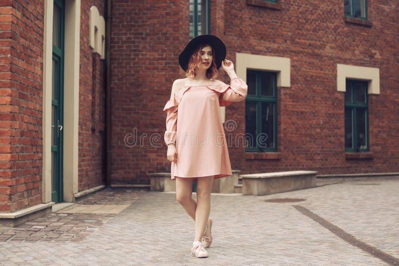 美丽的桃红色礼服和黑帽会议的女孩 女孩旅行 在游览中的女孩在欧洲 走通过美丽的街道的女孩 库存照片