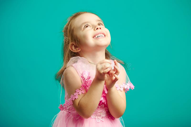美丽的桃红色礼服的惊奇的小女孩扣紧了在她前面的手并且愉快地查寻,画象  库存图片